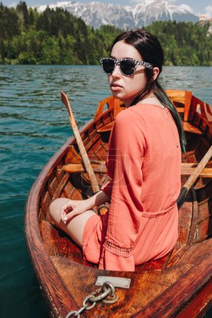 beautiful young woman in sunglasses sitting in boat at tranquil mountain lake, bled, slovenia