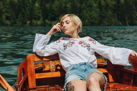 beautiful young woman with closed eyes sitting in wooden boat on lake