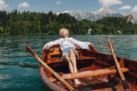 beautiful young woman resting in boat at tranquil mountain lake, bled, slovenia