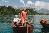 beautiful young women in boat at tranquil mountain lake, bled, slovenia