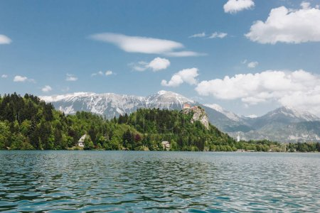 beautiful landscape with snow-covered mountain peaks, green vegetation and calm lake, bled, slovenia