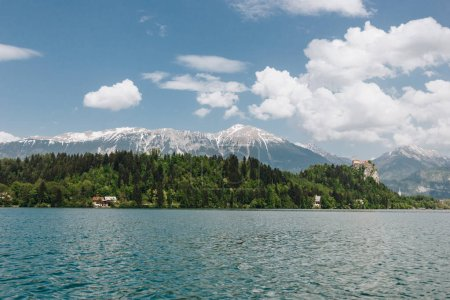 beautiful snow-covered mountain peaks, green vegetation and calm lake, bled, slovenia