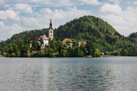 Photo pour Vue majestueuse sur les montagnes couvertes d'arbres verts, lac calme et bâtiments anciens, saigné, slovenia - image libre de droit