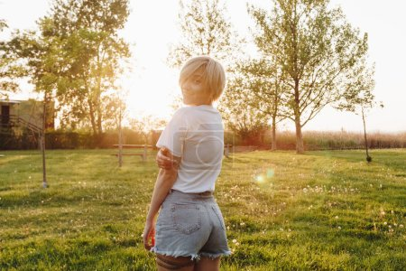 beautiful young woman in t-shirt and denim shorts looking at camera while standing on green lawn at sunset
