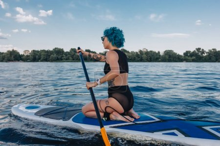 attractive tattooed woman with blue hair paddle boarding on river