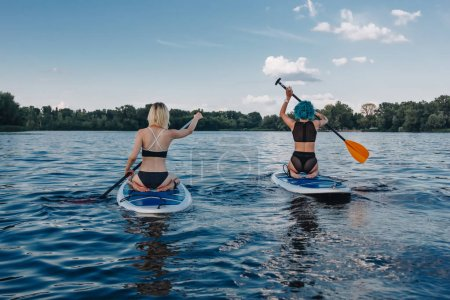 Photo for Back view of girls surfing on paddle boards on river - Royalty Free Image