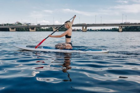 tattooed girl surfing on paddle board on river