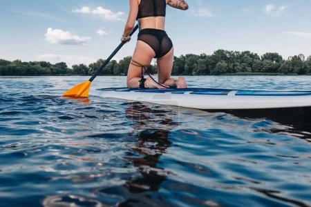 cropped view of tattooed girl surfing on paddleboard on river