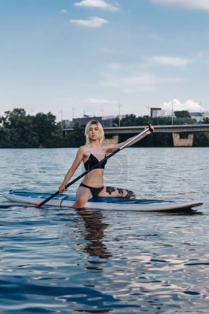sporty beautiful girl sitting on sup board on river