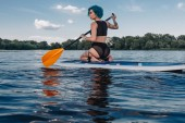 athletic tattooed girl sitting on paddle board on river