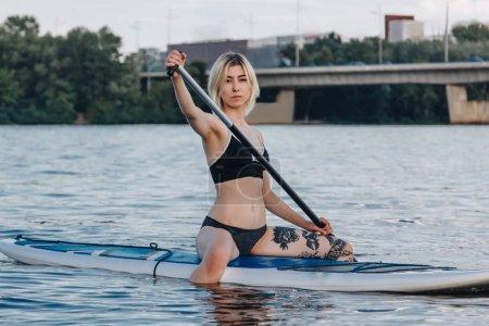 beautiful tattooed woman sitting on paddle board on river