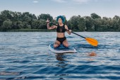 attractive tattooed girl with blue hair surfing on paddle board in water