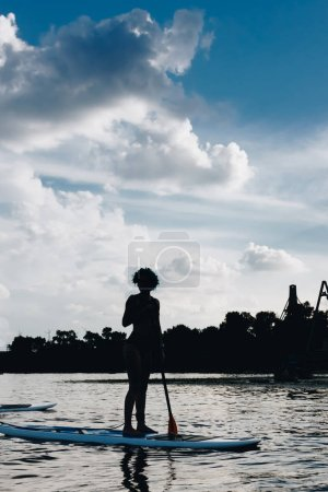 silhouette of sportswoman standing on paddle board on river with cloudy sky