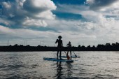 silhouettes of athletic women paddle boarding on river with cloudy sky