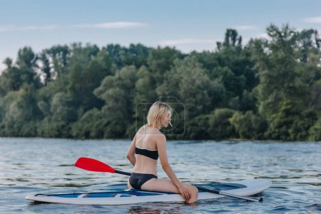 attractive blonde sportswoman sitting on paddle board on river