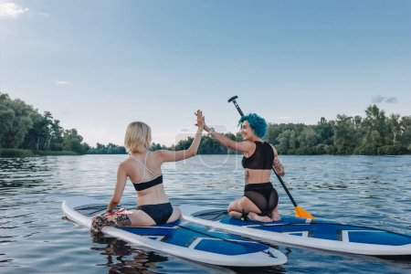 athletic women giving highfive while sitting on paddle boards on river