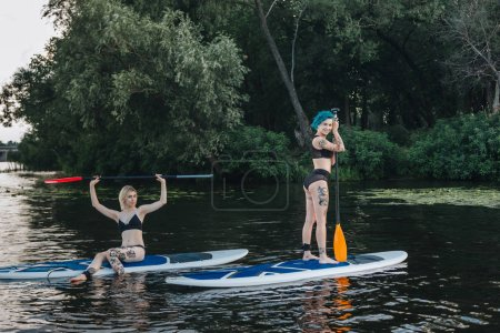 athletic women relaxing on paddle boards together on river