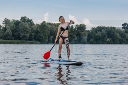 athletic tattooed girl in bikini surfing on sup board on river