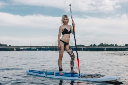 Photo for Beautiful blonde girl in bikini standing on paddle board on river - Royalty Free Image