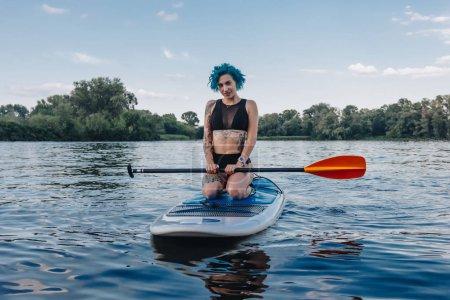 beautiful tattooed sportive girl sitting on paddle board on river
