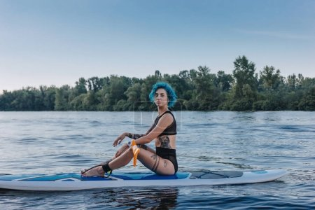 attractive tattooed sportswoman with blue hair relaxing on sup board on river