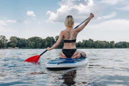 rear view of woman in black bikini sitting on paddle board on river