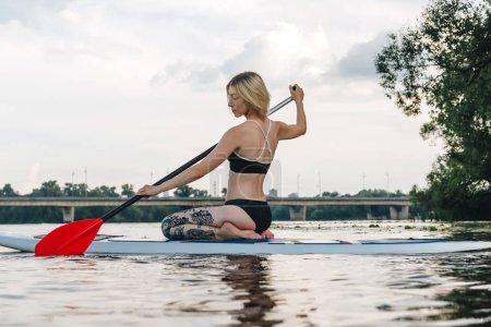 beautiful tattooed girl in black bikini sitting on sup board on river