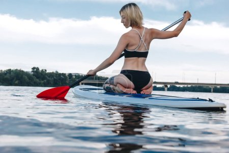 back view of girl in bikini surfing on paddle board on river