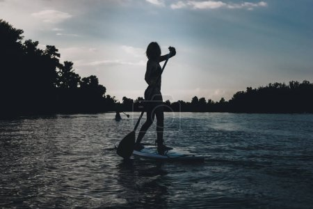 silhouette of athletic woman standup paddleboarding on river