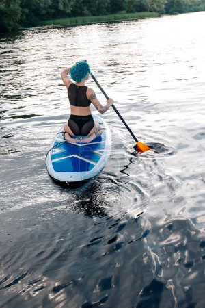 back view of sportive girl with blue hair paddle surfing on river