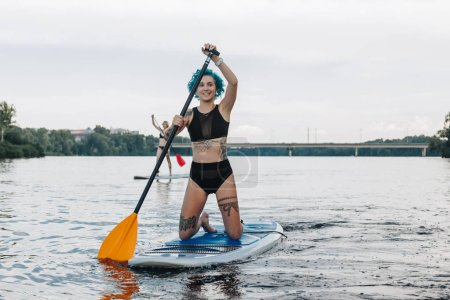 Photo for Attractive girls in bikinis surfing on paddleboards on river - Royalty Free Image