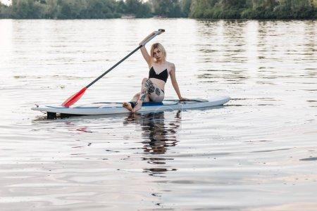 attractive tattooed sportswoman in bikini relaxing on paddle board on river