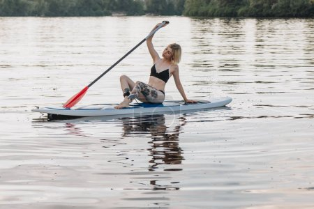 Photo for Beautiful tattooed girl in bikini resting on sup board on river - Royalty Free Image