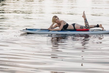 Photo for Athletic blonde girl relaxing on paddle board on river - Royalty Free Image
