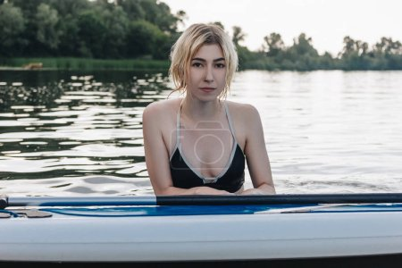 Photo for Portrait of blonde attractive girl with paddle board in water - Royalty Free Image