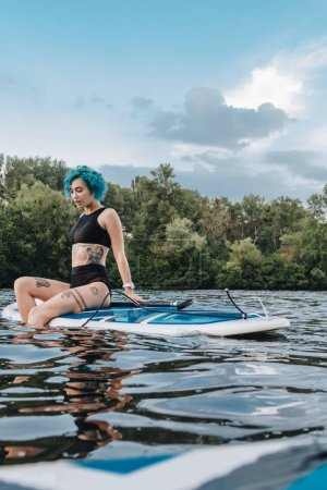 sportive tattooed girl sitting on paddle board on river