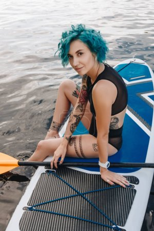 attractive athletic girl with blue hair resting on paddle board on river