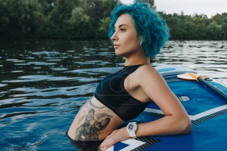 athletic young woman with blue hair relaxing on paddleboard in water