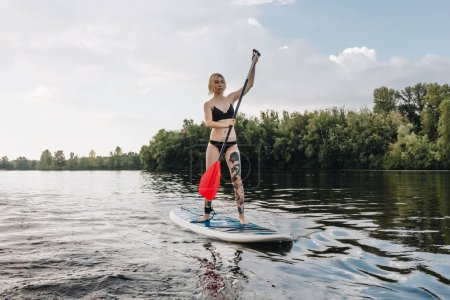 blonde athletic girl in black bikini standup paddleboarding on river