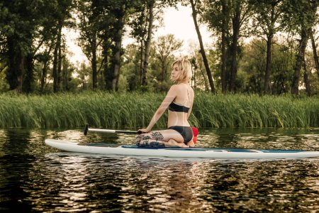 beautiful blonde girl sitting on paddle board on river