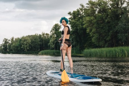 sportive young woman with blue hair standup paddleboarding on river