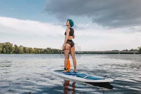 beautiful sportive young woman with blue hair standup paddleboarding on river