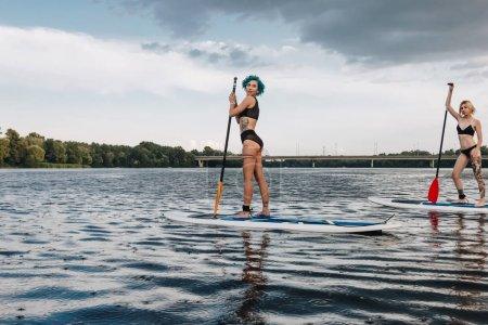 athletic tattooed women surfing on paddleboards on river