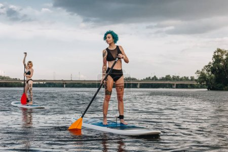 athletic women standup paddleboarding together on river