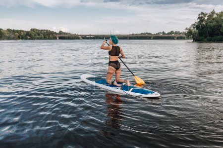 beautiful athletic tattooed woman in bikini paddle boarding on river