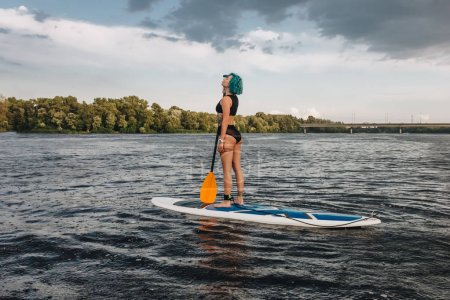 happy tattooed girl in bikini with blue hair paddle boarding on river