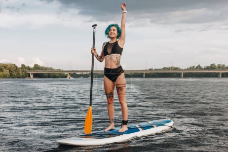 tattooed sportswoman waving and paddle boarding on river in summer