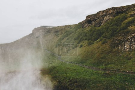 scenic view of landscape with steam and road leading through highlands in Iceland