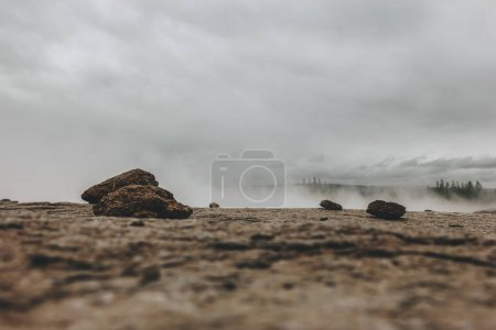 surface level of landscape with with stones and steam under cloudy sky in Haukadalur valley in Iceland