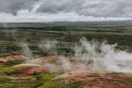 aerial view landscape with volcanic vents under cloudy sky in Haukadalur valley in Iceland